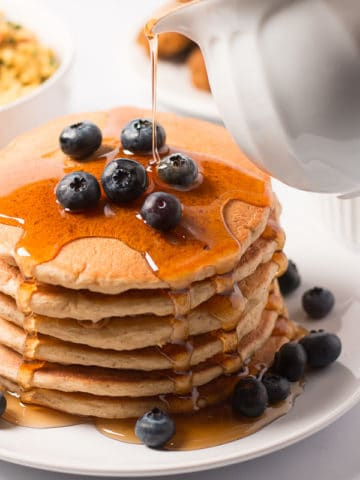 Maple syrup being poured over stack of pancakes topped with blueberries; breakfast sausage, tofu scramble, and blueberries in background