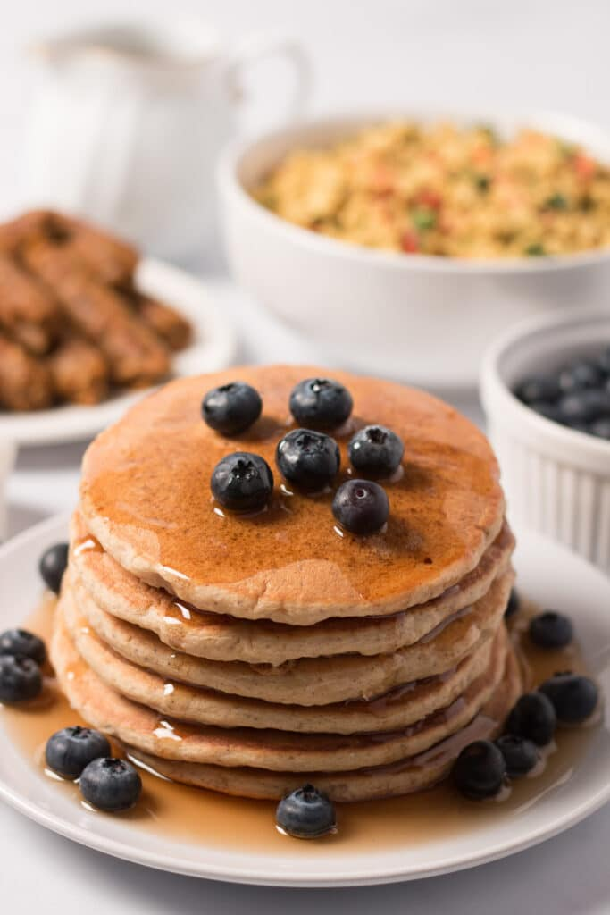 Stack of vegan whole wheat pancakes topped with blueberries and maple syrup; breakfast sausage, tofu scramble, and blueberries in background