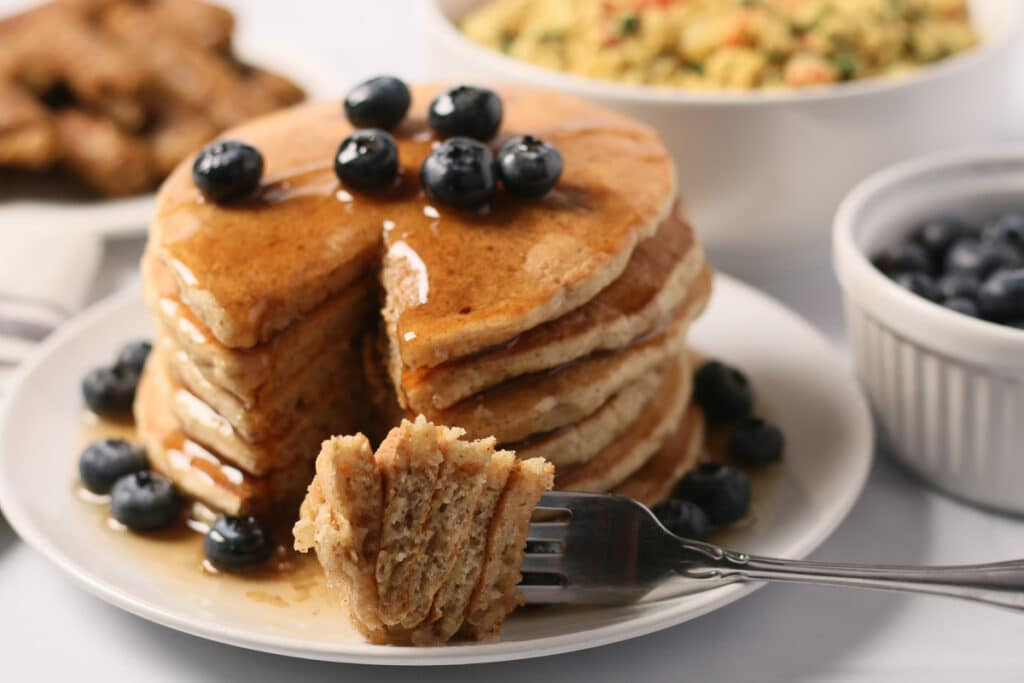 Stack of whole wheat vegan pancakes topped with blueberries and maple syrup, with forkful of pancake resting on plate; breakfast sausage, tofu scramble, and blueberries in background