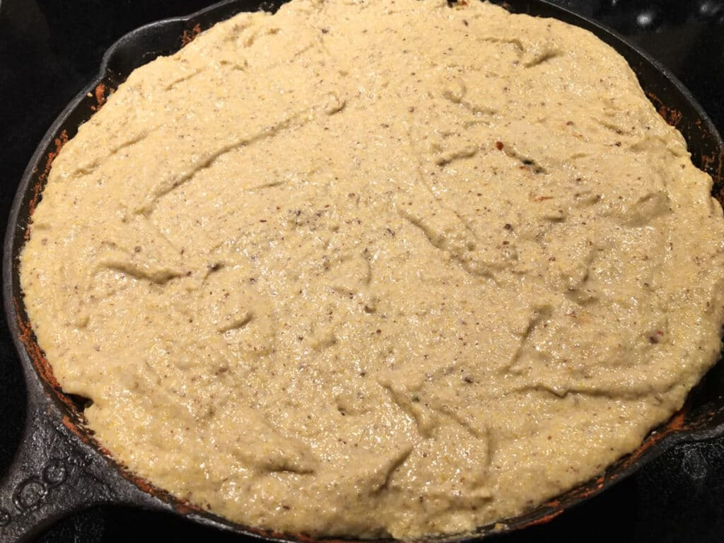 Cast iron skillet with tamale pie ready to go in the oven
