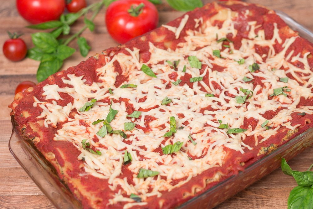 Pan of lasagna with tomatoes and basil in background