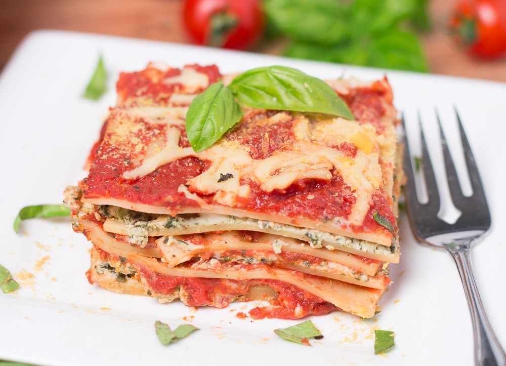 Serving of dairy free lasagna on white square plate with basil garnish and tomatoes & basil in background
