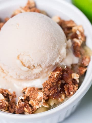 Small white bowl of apple crisp with a scoop of vanilla ice cream, two green apples beside it