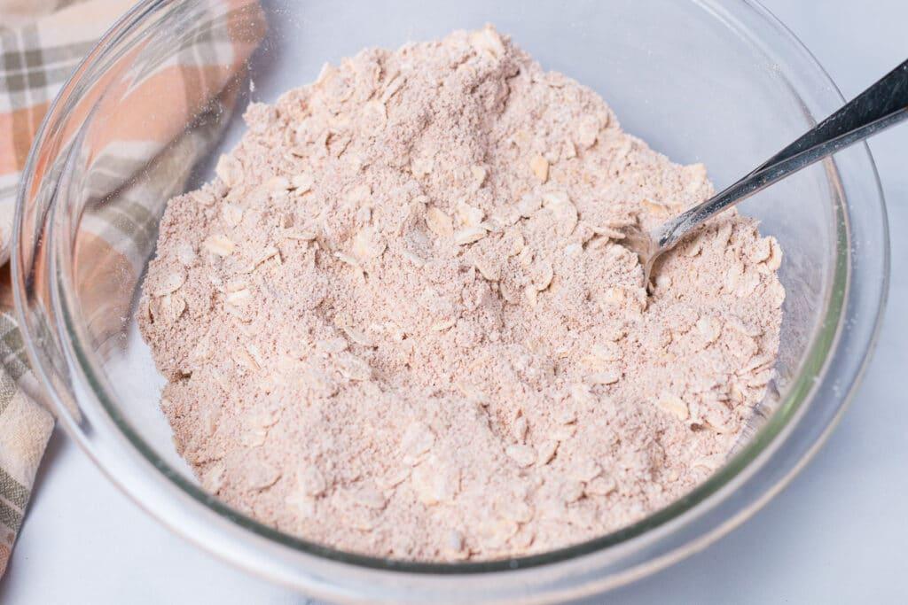 Glass bowl with flour, sugar, oatmeal and cinnamon mixture