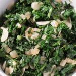 Closeup shot of kale, garlic & onions in a white bowl