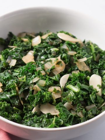 White bowl of cooked kale, garlic & onions, pink napkin and metal tongs beside it
