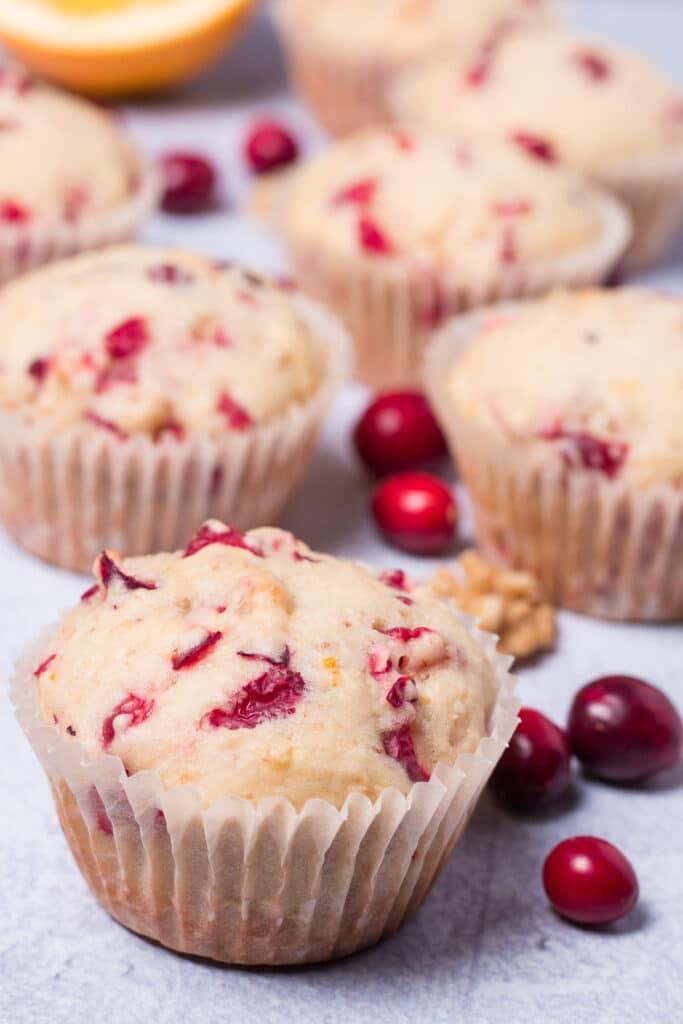 Vegan cranberry orange muffins with fresh cranberries scattered around them