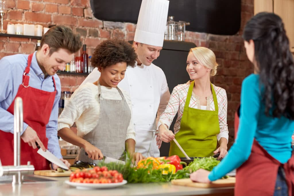 Friends and a chef cooking a plant based meal in a kitchen