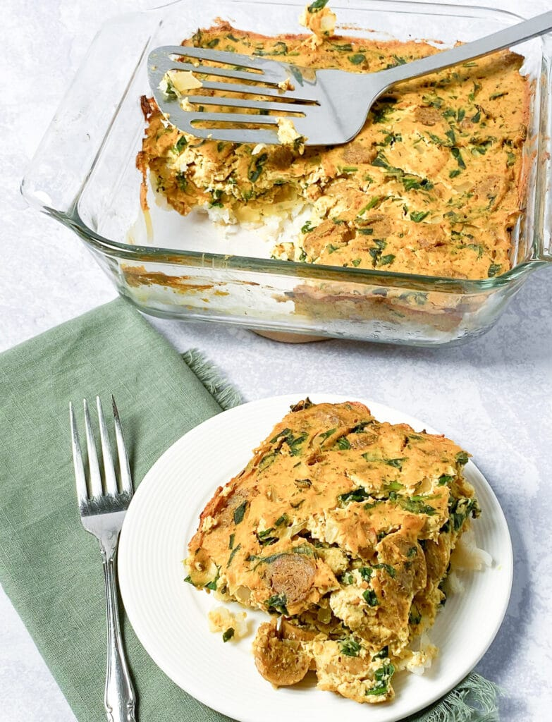 Serving of breakfast casserole with pan of casserole in background, green napkin and fork beside plate