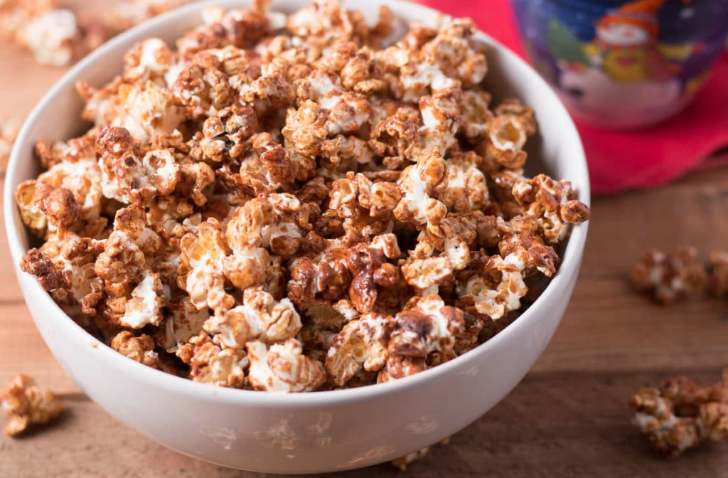 Bowl of gingerbread popcorn with holiday cup and red napkin behind it