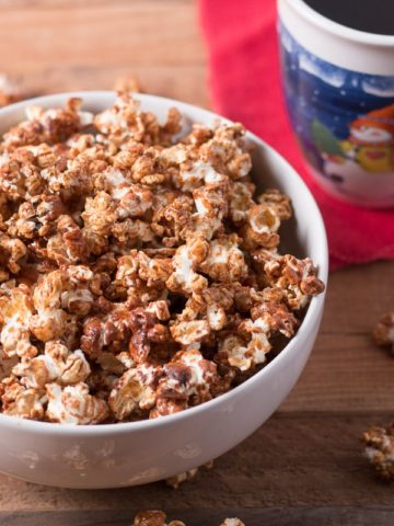Bowl of gingerbread popcorn with cup of coffee and red napkin behind it