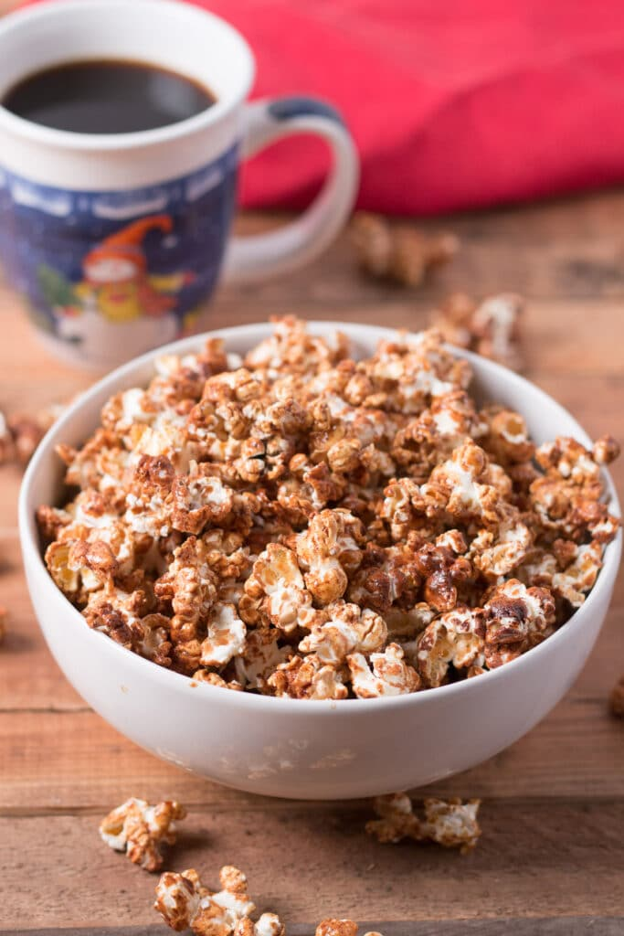Bowl of gingerbread popcorn with cup of coffee and red napkin in background