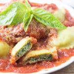 Plate of ravioli with tomato sauce topped with basil leaves; one ravioli cut in half