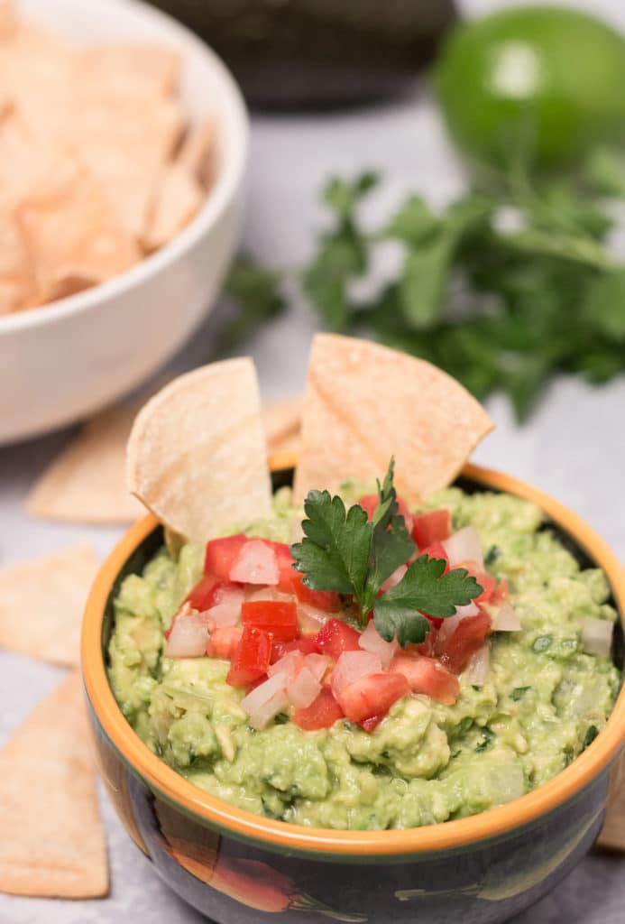 Bowl of guacamole with cilantro, lime, avocado, and bowl of chips in background