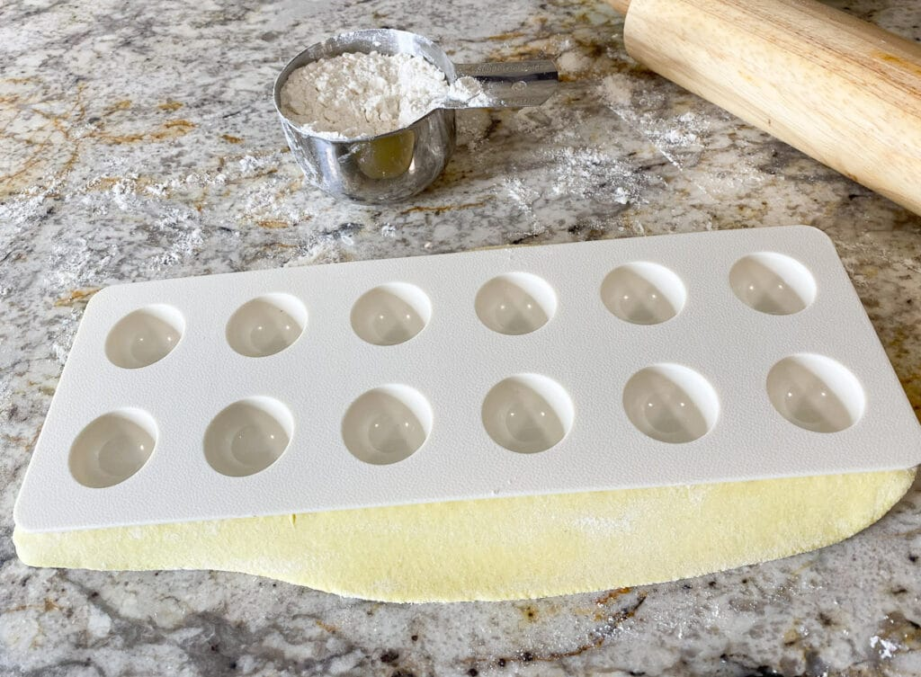 Plastic insert pressing dough to prepare for ravioli filling, cup of flour and rolling pin in background