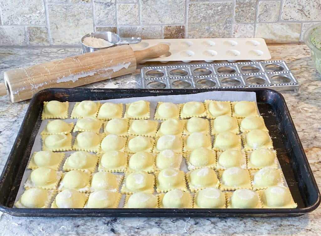 Baking sheet full of finished ravioli with ravioli press, cup of flour, and rolling pin in background