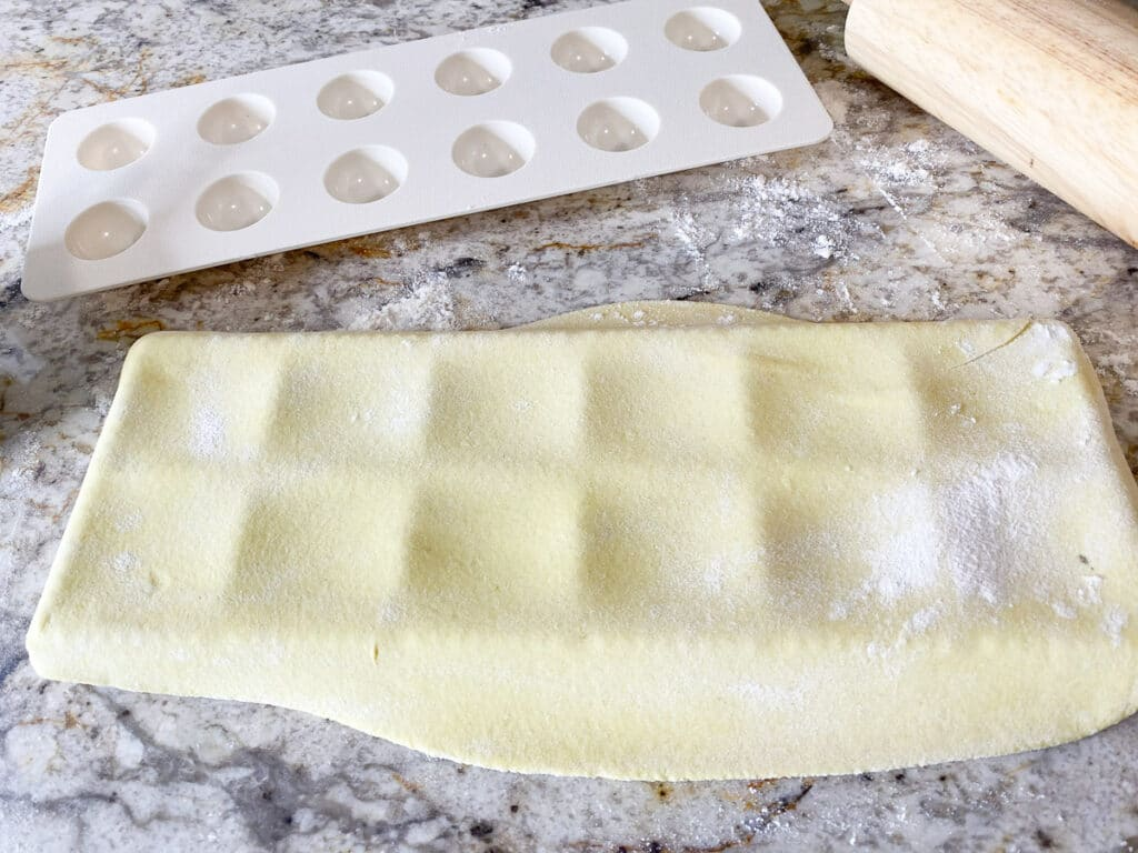 Layer of pasta dough layed over the ravioli maker, with plastic ravioli pressing tray and rolling pin in background