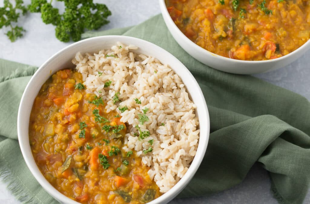 Two bowls of red lentil dal and rice with green napkin and sprig of parsley