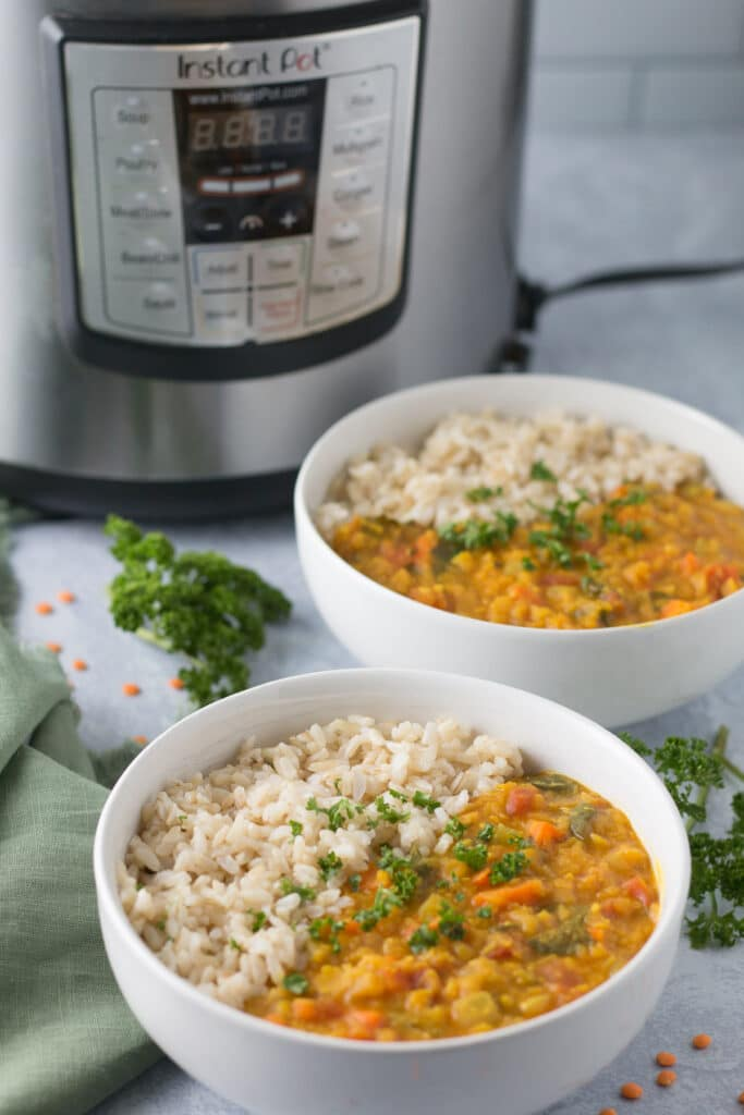 Two bowls of dal and rice with Instant Pot in background