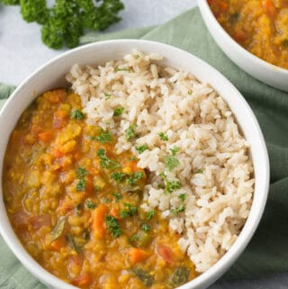 Two bowls of red lentil dal and rice with green napking and sprig of parsley