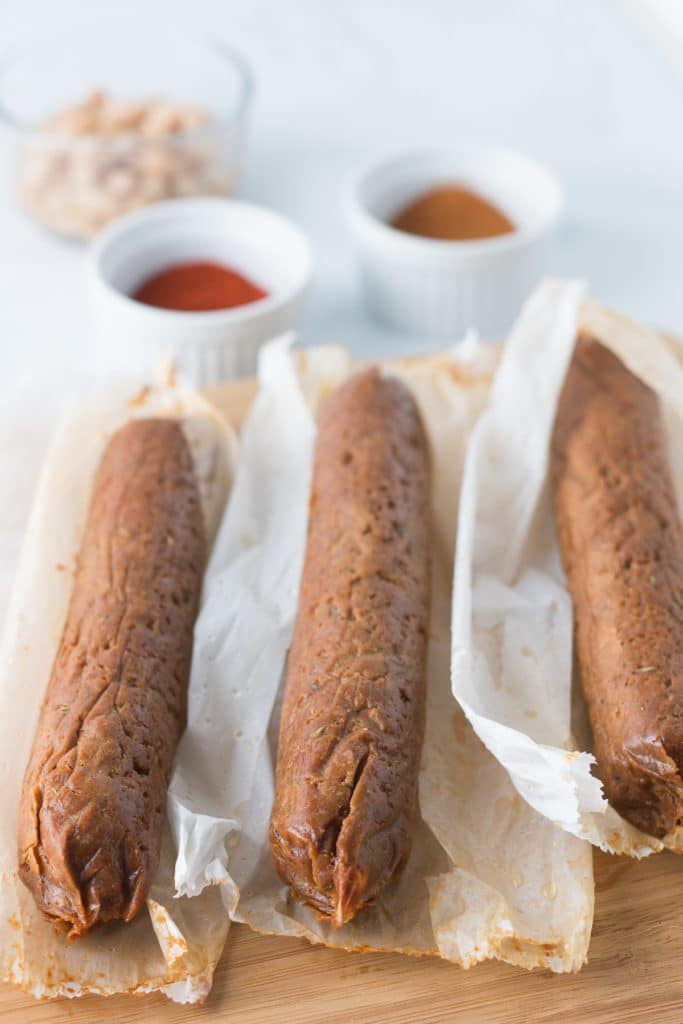 Three sausages on parchment paper wrapping, bowls of spices and beans in background