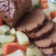 Closeup image of slilced vegan ham on platter with potatoes and carrots
