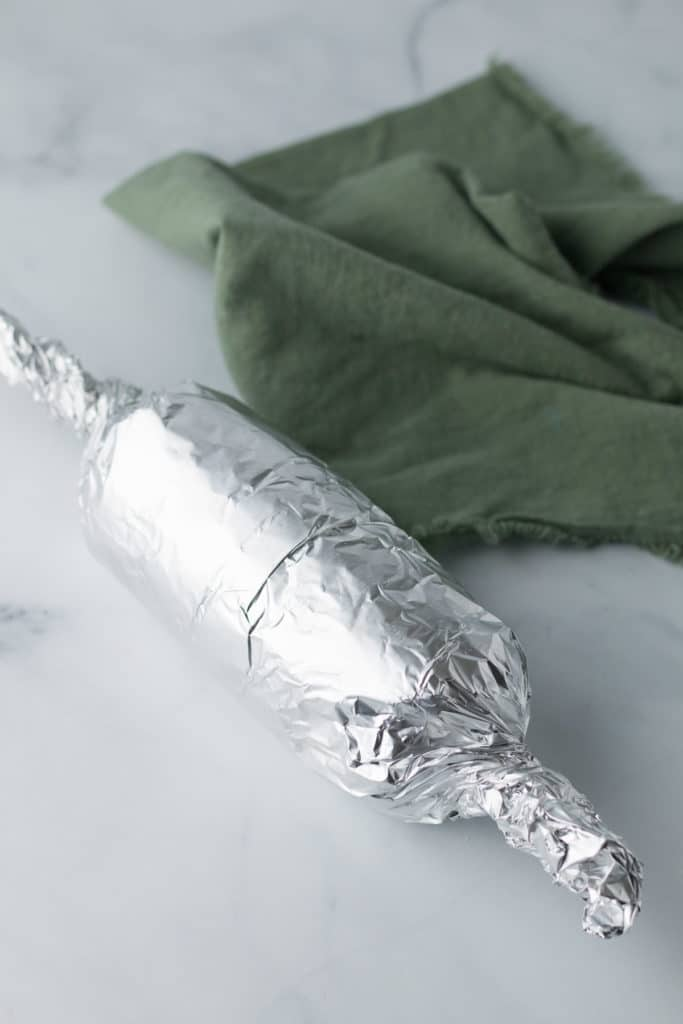 Seitan dough wrapped in foil with green napkin beside it