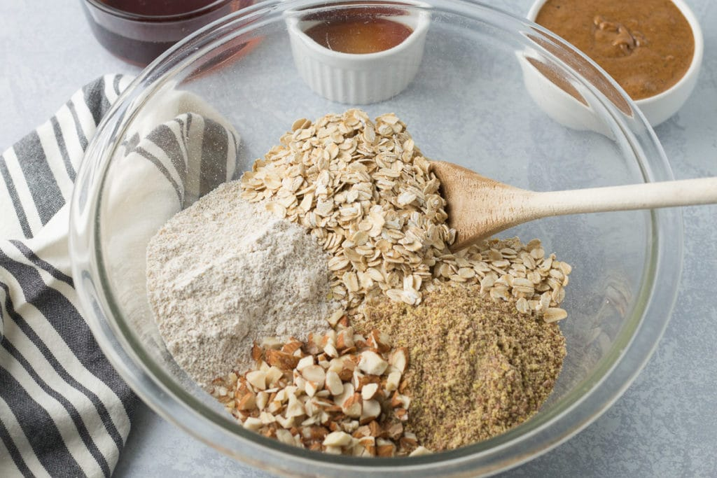 Bowl of dry ingredients for granola bars with wet ingredients in background.