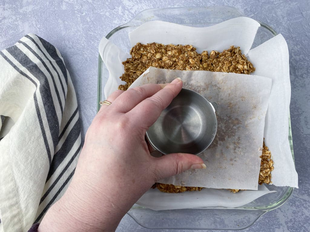 Granola being pressed into baking pan with a measuring cup and parchment paper