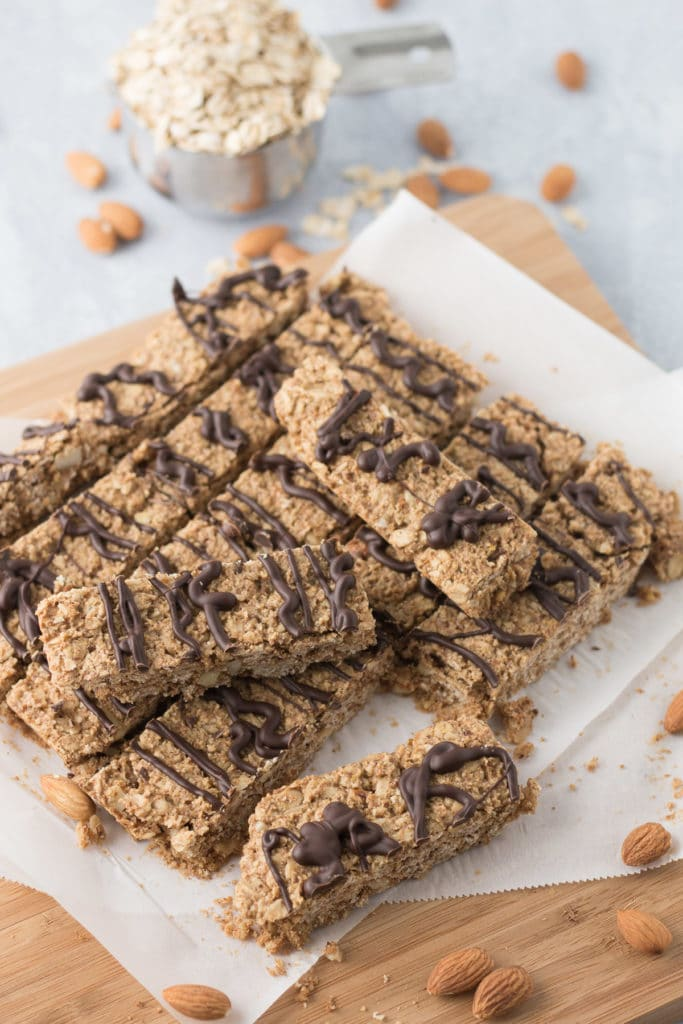 Granola bars on parchment covered cutting board with almonds and cup of oats in background