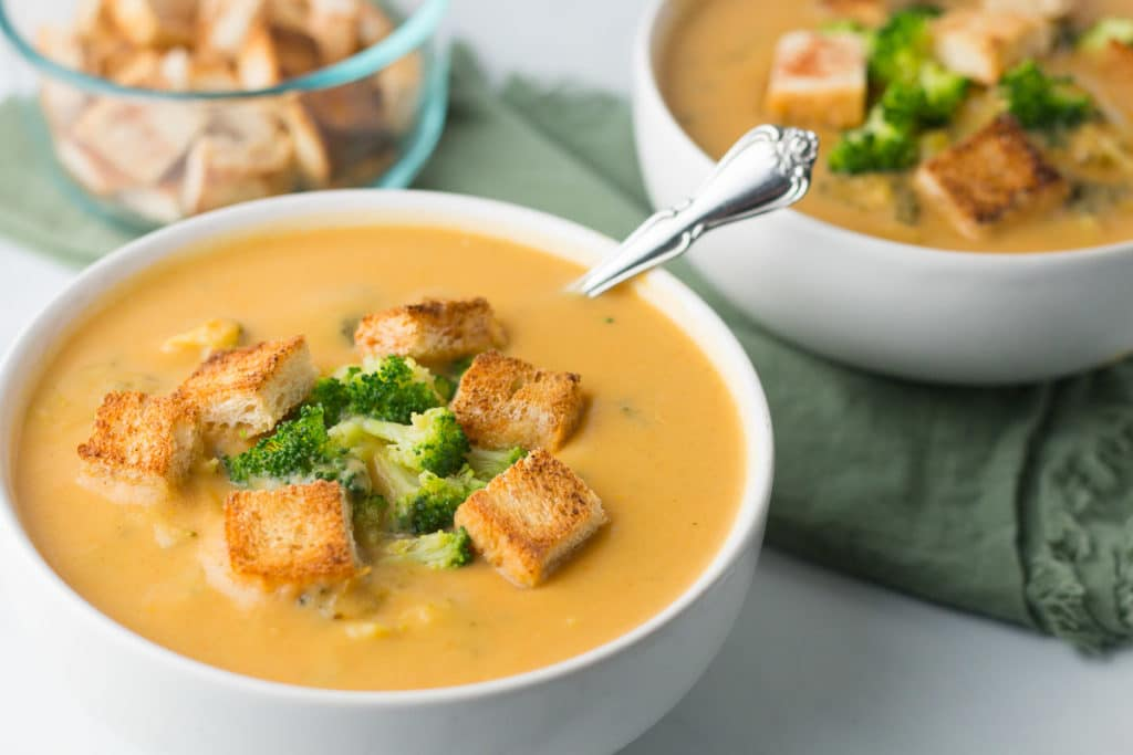 Two bowls of broccoli cheddar soup with bowl of croutons in background