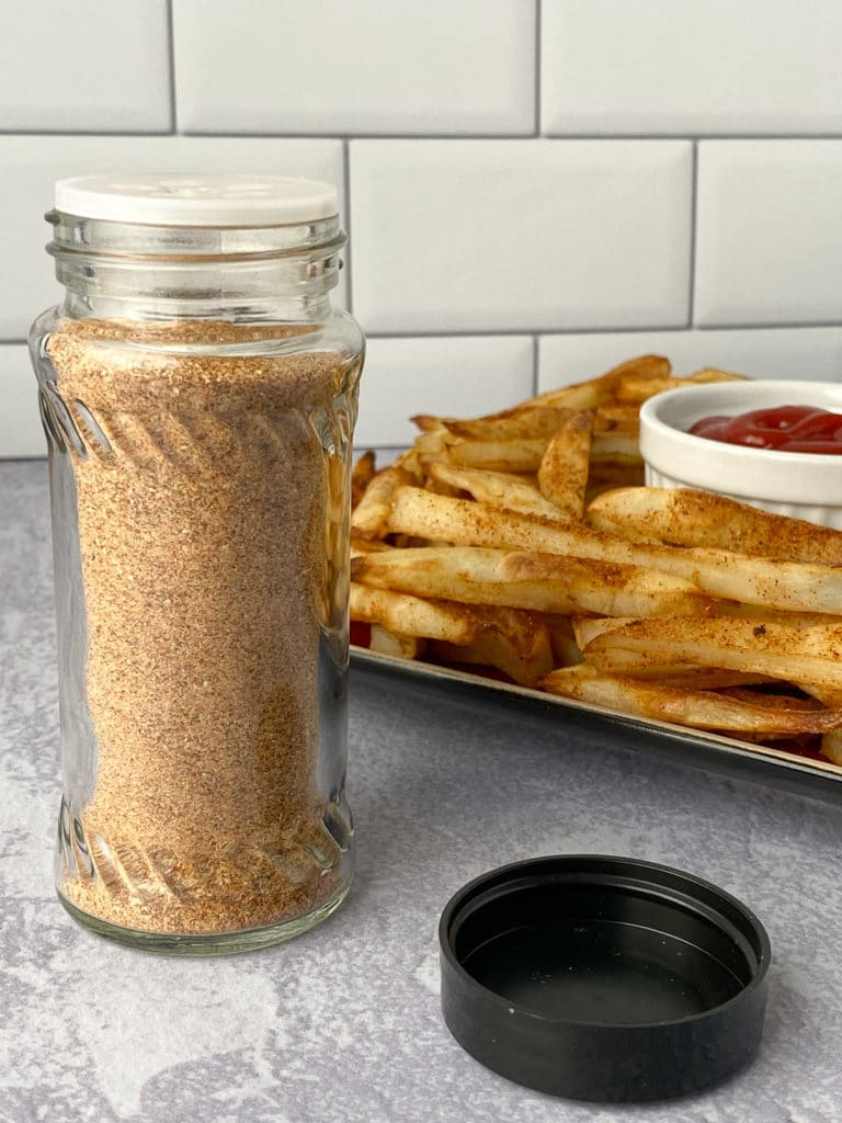 Jar of seasoning with plate of fries in background
