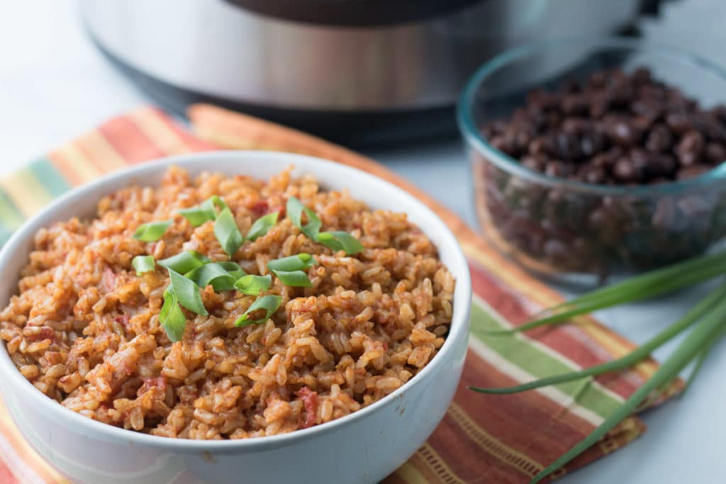 White bowl of Mexican rice in front of bowl of black beans and Instant Pot