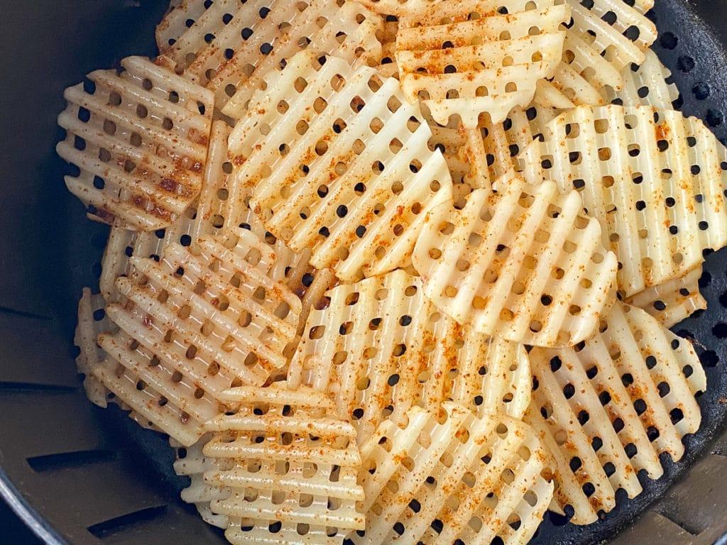 Seasoned waffle sliced potatoes in air fryer basket