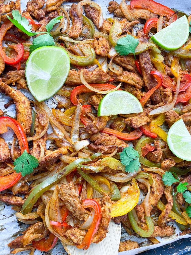 Baked soy curl fajita filling on a baking pan, garnished with cilantro and lime