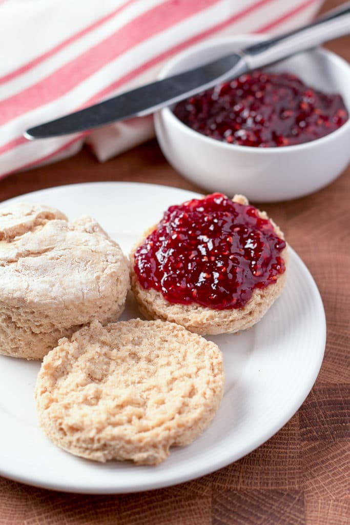Plate with split biscuit with jam and whole biscut; bowl of jam, knife, and napkin in background
