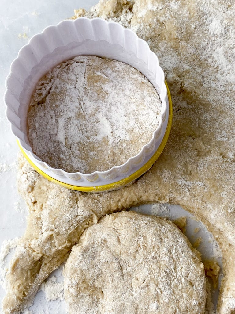 Biscuits being cut from dough with biscuit cutter