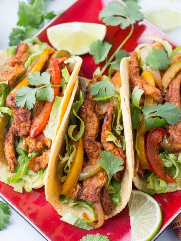 Three fajitas on a red plate, garnished with cilantro and lime slices, with striped napkin and bowl of lettuce beside the plate.