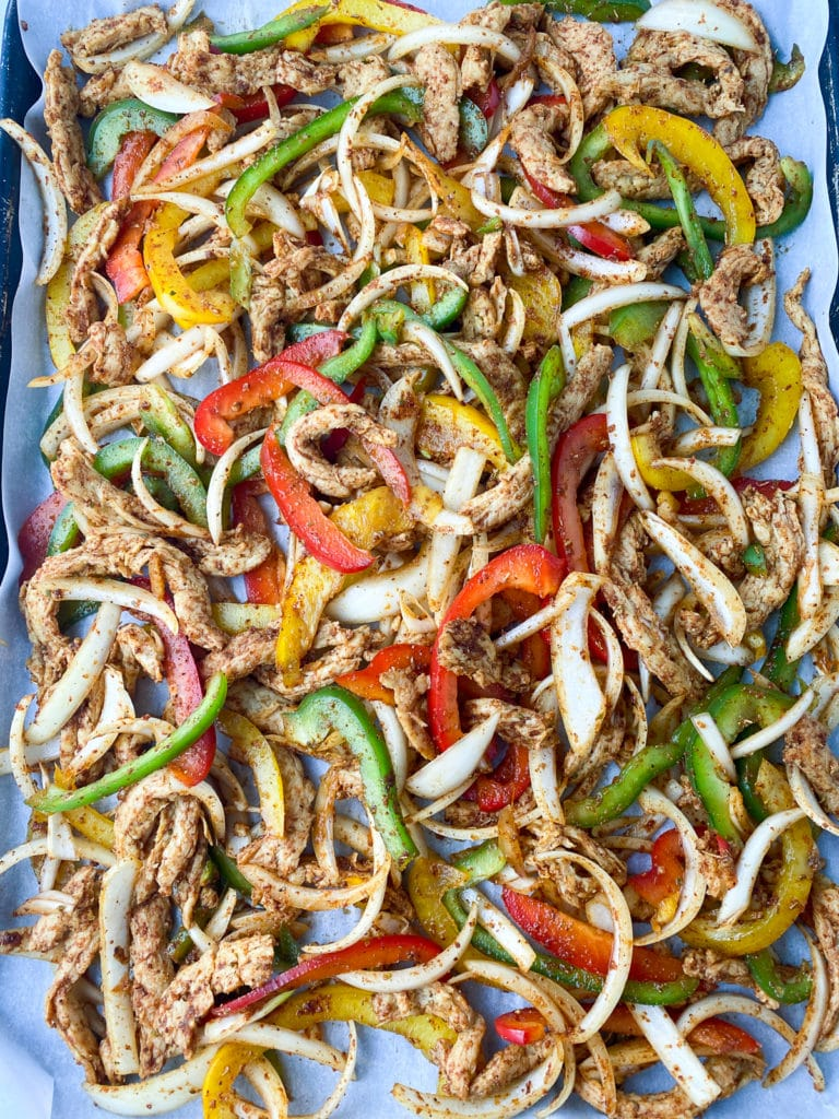 Unbaked fajitas on parchment covered pan