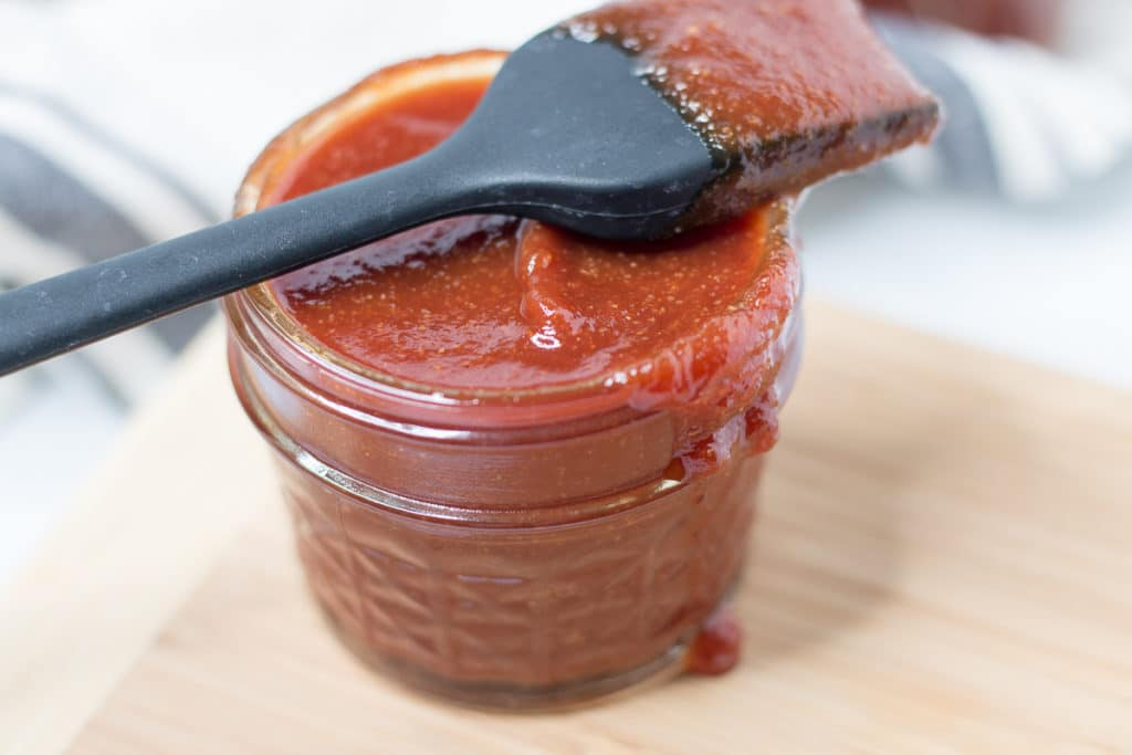 Jar of sauce with basting brush resting on top of jar