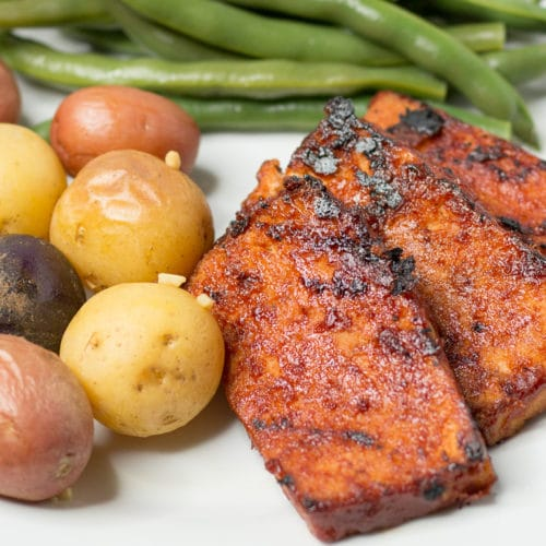 White plate with bbq tofu slices, baby potatoes, and green beans