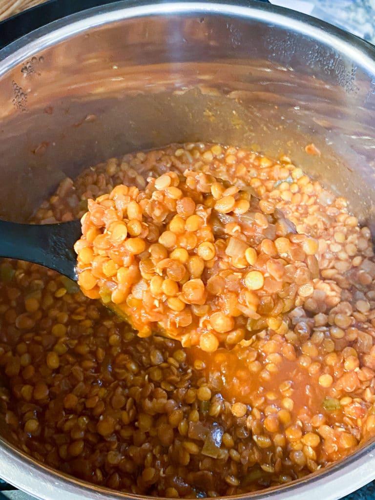 Scoop of lentil sloppy joes held over pot of sloppy joes
