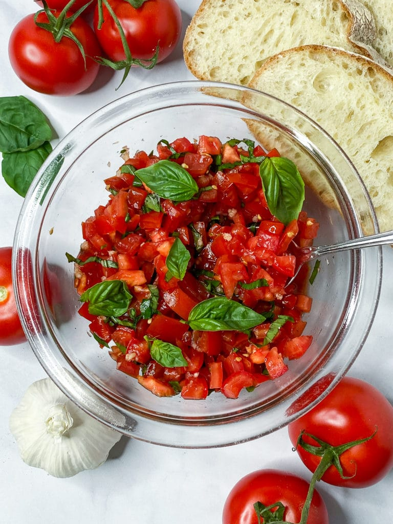 Bowl of tomato basil topping surrounded by bread, tomatoes, and basil