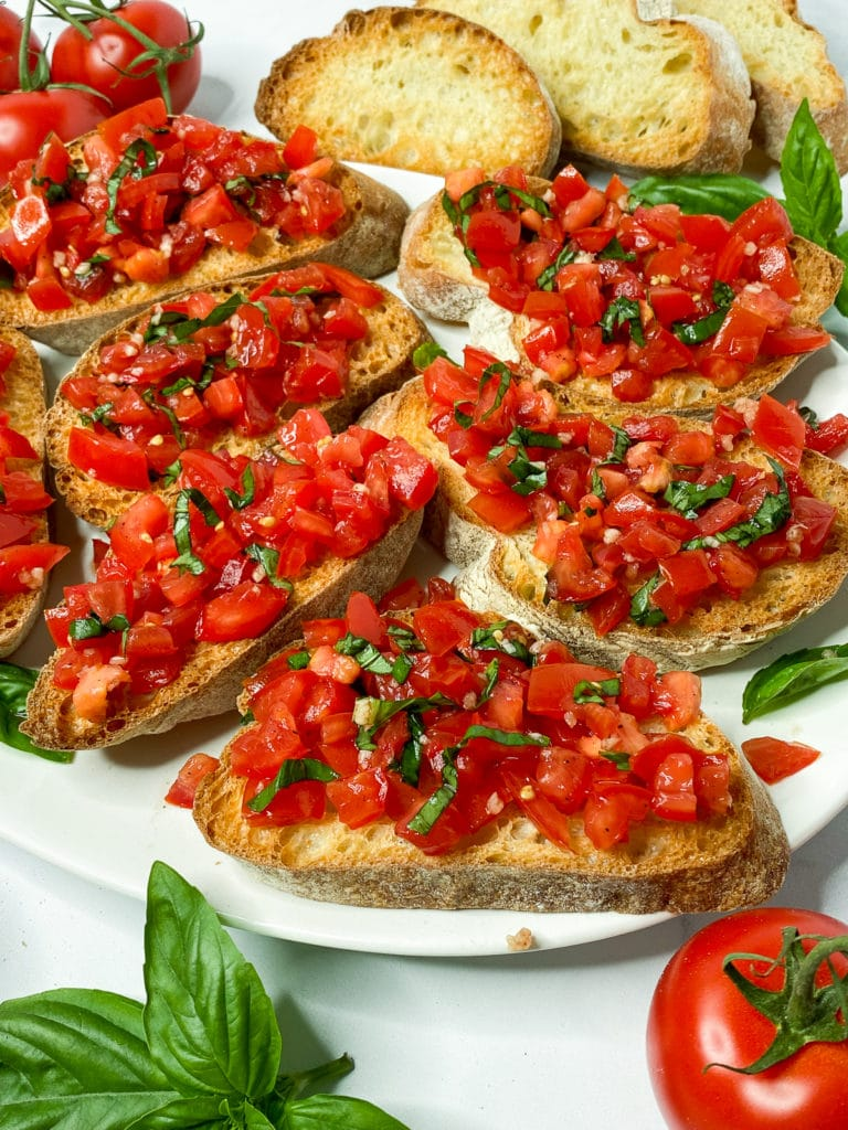Platter of tomato bruschetta surrounded by tomatoes, basil, and toasted bread