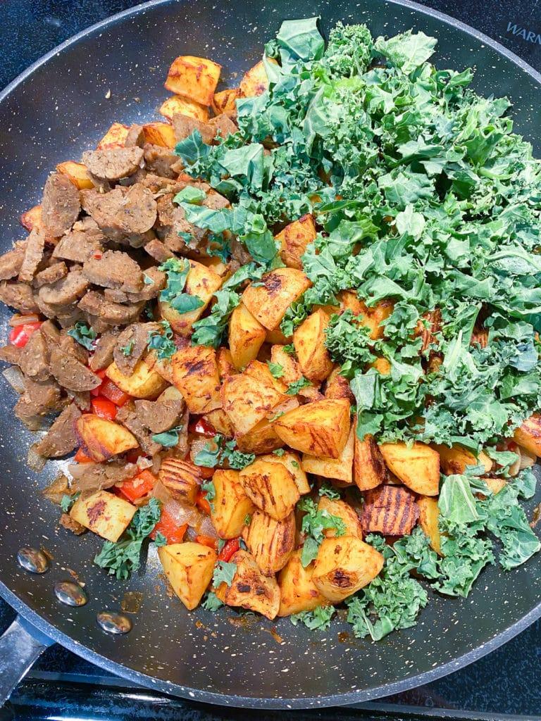 Final ingredients added to skillet for vegan breakfast hash