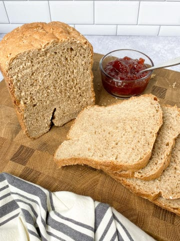 Loaf of bread sliced on a cutting board with knife and bowl of jam next to it
