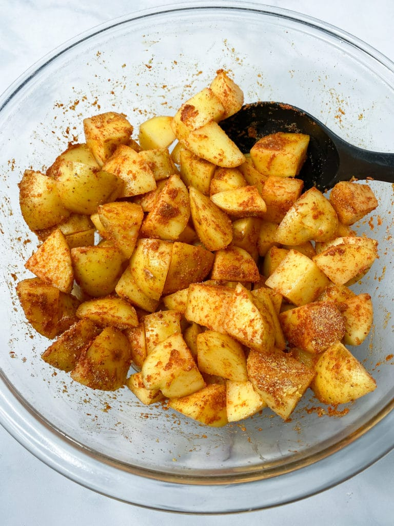 Glass bowl of diced potatoes coated with seasoning