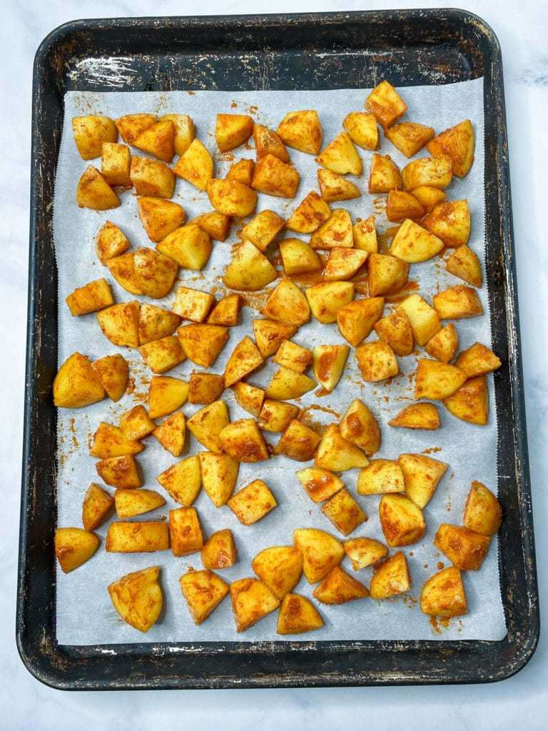 Seasoned diced potatoes on a parchment lined baking sheet