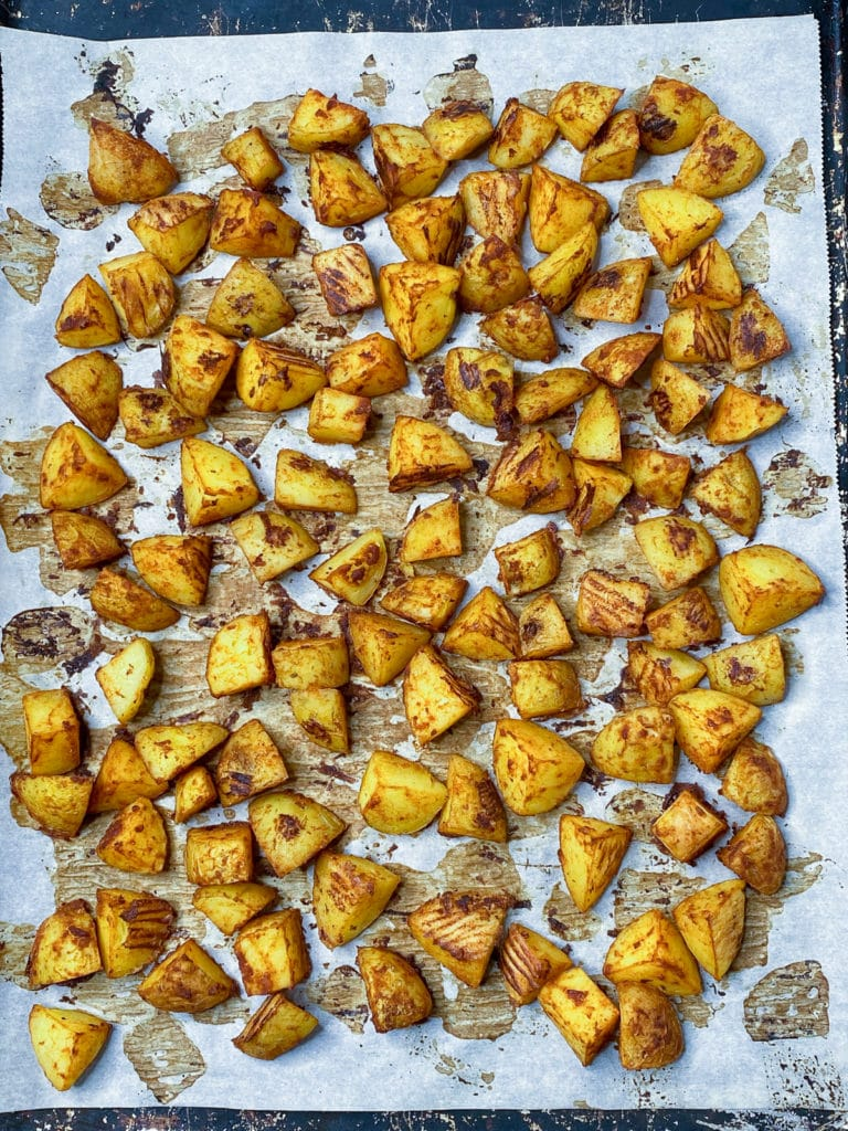 Roasted seasoned potatoes on a parchment lined baking sheet